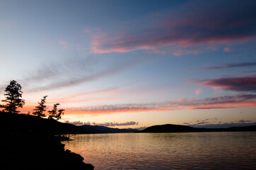 Silhouette of a lakeside with trees during sunset with pink clouds, Mongolia