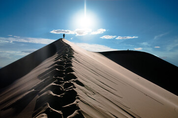 Man walking in footprints in the Gobi Khongoryn Els, on the top of one of the sand dunes, Gobi, Mongolia