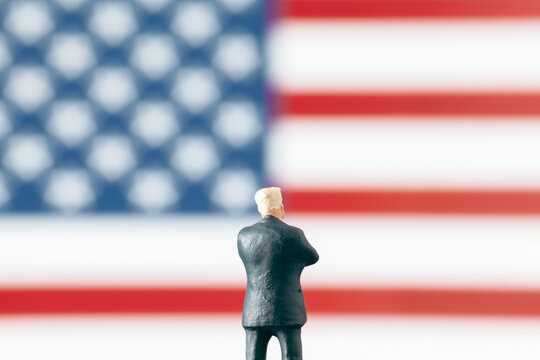 Business world  or politics concept: Miniature figurine with arms crossed looking at defocused USA flag. Leadership and success in business world.