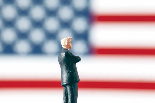Business world  or politics concept: Miniature figurine with arms crossed standing in front of defocused USA flag. Leadership and success in business world.