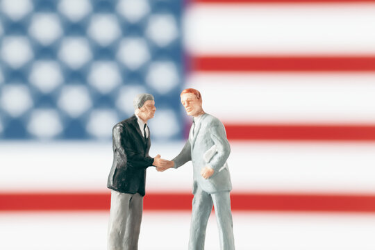 Agreement or negotiation in world politics concept: Miniature figurines shaking hands in front of defocused United States of America flag.