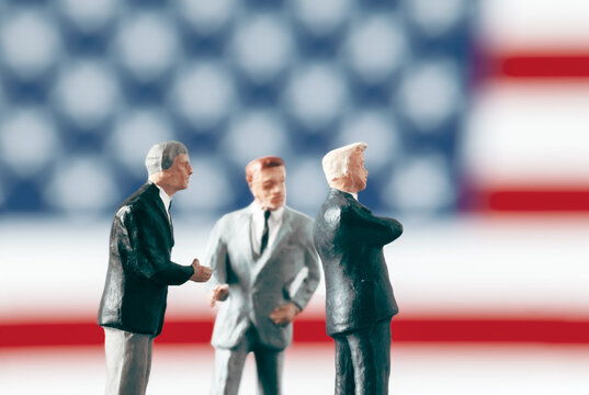 Discussion and conflict in politics concept: Miniature politician figurines discussing about a subject in front of defocused United States of America flag. Leadership and success in business world.