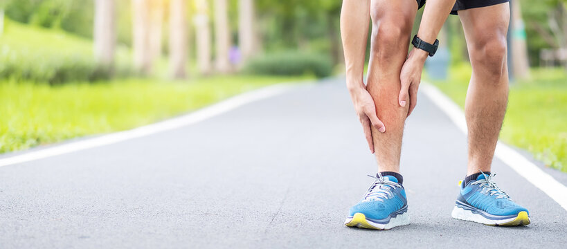 Young adult male with his muscle pain during running. runner man having leg ache due to Shin Splints. Sports injuries and medical concept