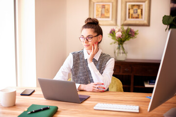 Thinking woman using laptop while sitting at desk at home daydreaming