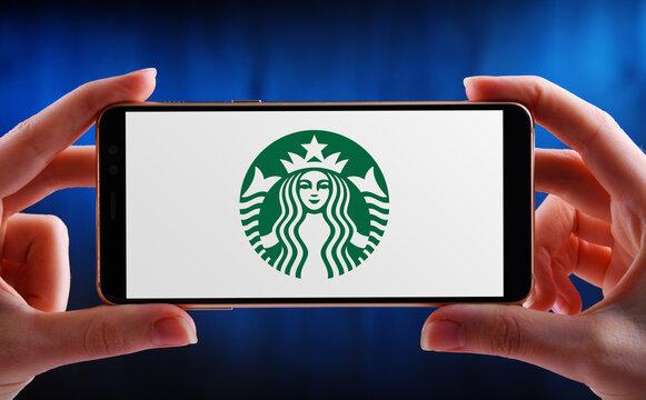 Hands holding smartphone displaying logo of Starbucks