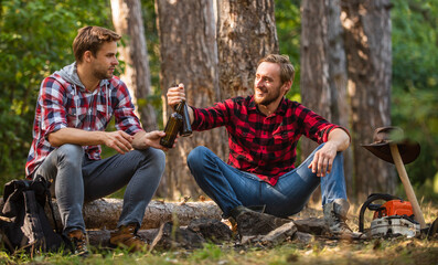 Away From The City. hiking and camping. male friendship. man best friend drink beer. ranger at outdoor activities. picnic weekend in nature. Tourism concept. hike and people. two men relax in forest