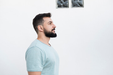 Bearded man with white wall background, outdoors shot