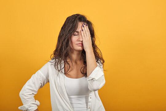 Closing face palm covers eyes visible through with hands. Young attractive woman, dressed white blouse, with brown eyes, curly hair, yellow background