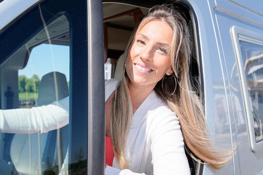 beautiful happy woman driver in motor home rv camping van in lifestyle vanlife