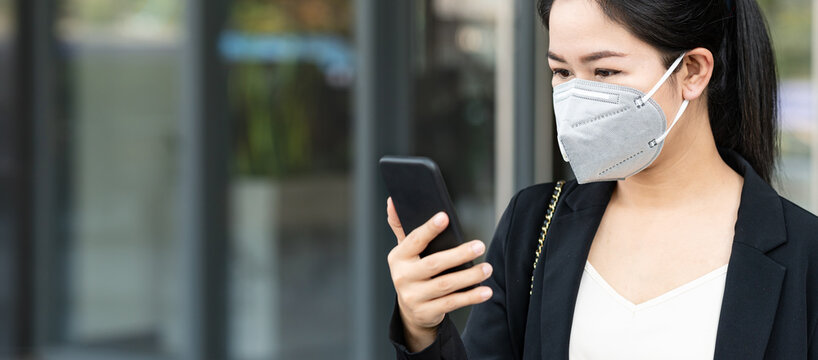 Panoramic of young happy asian businesswoman worker wear n95 facemask smile and look at mobile phone in concept back to work after covid crisis, go to work outside or outdoor, work anywhere concept.