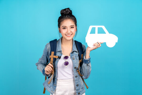 Portrait of young happy carefree asian woman holding white paper car in concept of back to domestic travel, travel bubble, insurance service care or protection, auto finance, secure cover or coverage.
