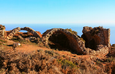 A historic old fortress with brick arches high in the mountains of the Sierra de Bernia on Spain's east coast, on the Costa Blanca. In the background the blue one. Mediterranean Sea.