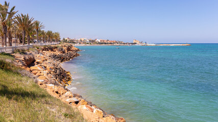 A rocky stretch of coast in front of a sandy beach. On the right is the small boat marina at Torre de La Horadada. It is summer and the sun is shining with a blue sky.