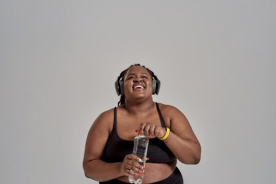 Tomorrow is looking great. Plump, plus size african american woman in sportswear and headphones laughing, opening bottle of water, posing in studio over grey background