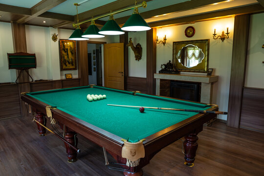 Billiard room interior. Green table for game. Old german style design. Brown wooden decor on the ceiling, walls and floor.