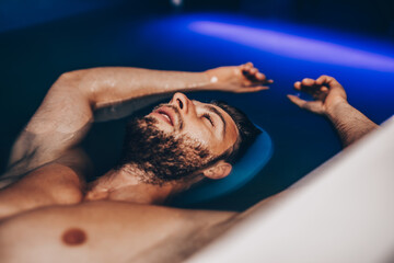 Handsome beard man floating in tank filled with dense salt water used in meditation, therapy, and alternative medicine.