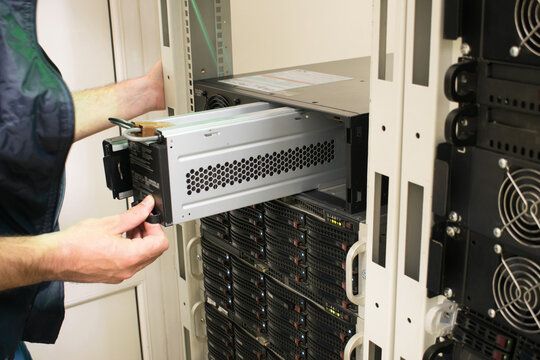 Changing the power module in the server room close-up. Working with equipment in the datacenter rack. Replacing the battery in an uninterruptible power supply.