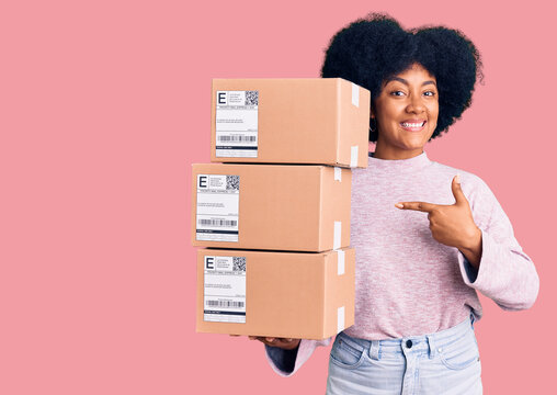 Young african american girl holding delivery package smiling happy pointing with hand and finger