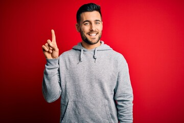 Young handsome sportsman wearing sweatshirt standing over isolated red background showing and pointing up with finger number one while smiling confident and happy. Fotomurales