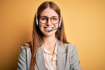 Young redhead call center agent woman overworked wearing glasses using headset happy face smiling...