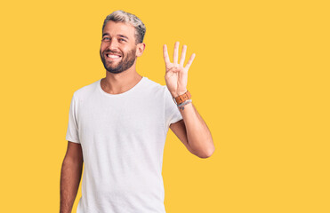 Young handsome blond man wearing casual t-shirt showing and pointing up with fingers number four...