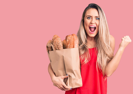 Young beautiful blonde woman holding paper bag with bread screaming proud, celebrating victory and success very excited with raised arms