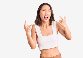 Young beautiful chinese girl wearing casual clothes shouting with crazy expression doing rock...