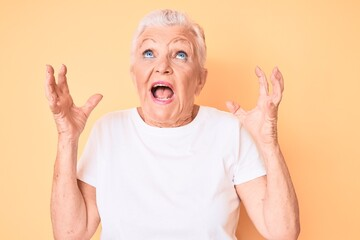 Senior beautiful woman with blue eyes and grey hair wearing classic white tshirt over yellow...