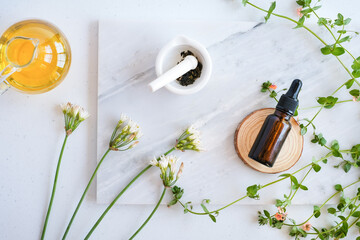 natural skincare serum in dropper bottle on marble background with flower, leaf and pestle mortar . cosmetic beauty background.