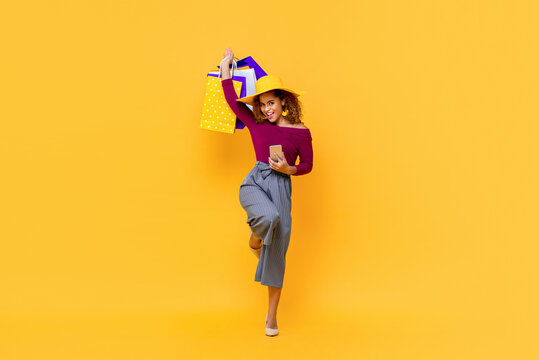 Fun full length portrait of happy young attractive shopaholic African American woman raising shopping bags and holding mobile phone in isolated studio yellow background