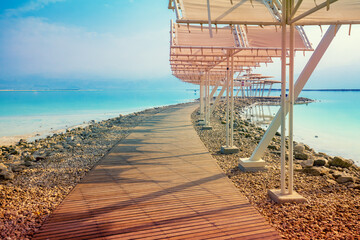 Fototapete - Seascape. The shore of the Dead Sea. Beach with a wooden walkway and sunshades. Summer. Israel