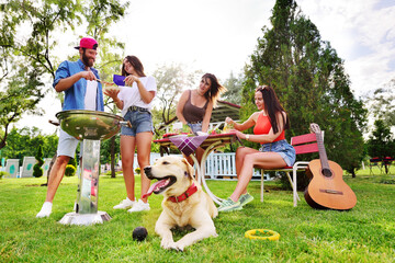 the Labrador Retriever dog is lying on the grass. A group or group of friends relax in nature, roast meat on the barbecue, play the guitar and smile against the background of greenery