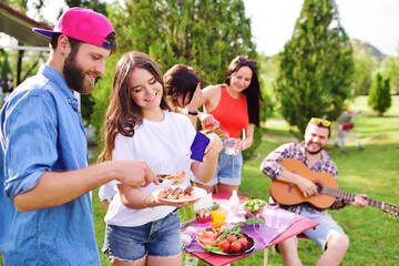 a young happy couple of a guy and a girl pour tomato sauce or ketchup on fried sausages against the background of a group of friends at a picnic table against the background of a Park,