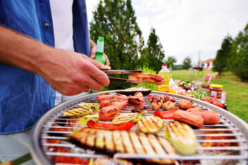 close-up of a man's hand holding a barbecue tongs with a delicious fried sausage on the background of a barbecue grill with sausages, vegetables, baked zucchini and pepper, beer bottles