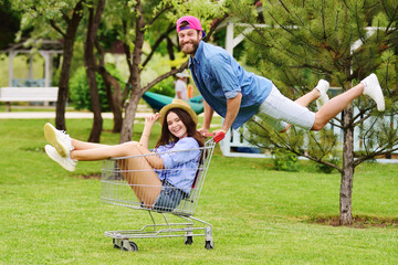 a young bearded man in a denim shirt and a pink cap is driving a young, pretty, smiling woman in a straw hat in a supermarket cart against a background of greenery and a Park.