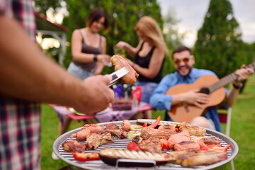a man's hand holds a barbecue tongs with a juicy delicious meat steak against the background of a barbecue grill with meat and vegetables and a group of friends on a picnic who are having fun