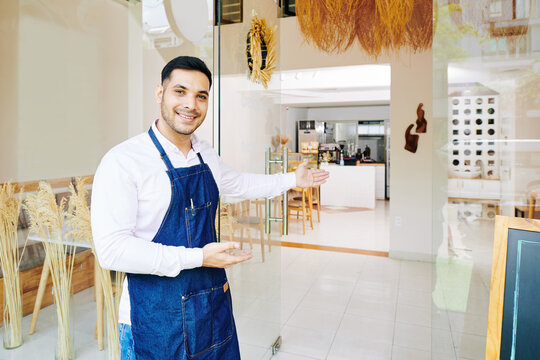 Handsome smiling bakery owner in apron making welcome gesture and inviting customers inside