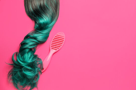 Unusual wig and brush on color background
