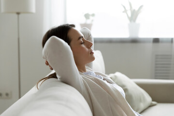 Side view calm woman closed eyes enjoy fresh conditioned air rest at home leaned on comfy couch. No...