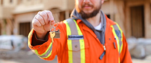 Banner of engineer giving keys from new house on construction site in the USA.