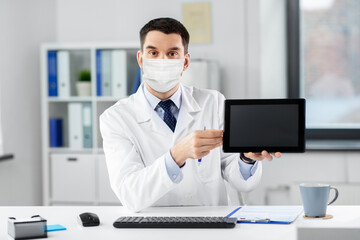 healthcare, medicine and people concept - male doctor in medical mask with tablet pc having video...