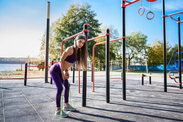 Beautiful  young female doing exercises on the street of the playground. Concept of good physical shape and healthy lifestyle