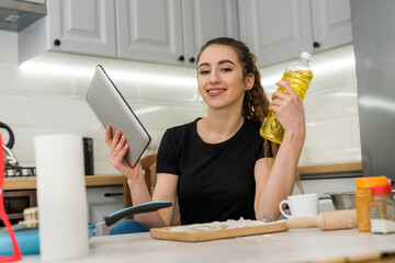 young pretty wife preparing cookies at home with help digital tablet