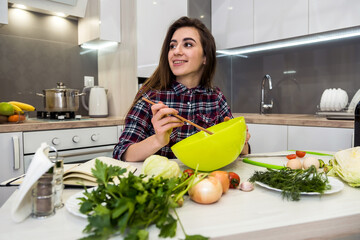 cute girl prepares a salad of different vegetables and greens for a healthy lifestyle.