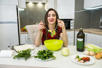 Pretty girl eating salad of fresh vegetables while smiling and sitting in the kitchen at home