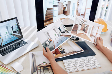 Obraz Interior designer sitting at desk and looking at printed photos of clients rooms after renovation - fototapety do salonu