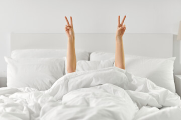 Deurstickers Wanddecoratie met eigen foto gesture, comfort and morning concept - hands of young woman lying in bed and showing peace hand sign at home bedroom