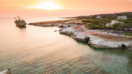 Aerial bird's eye view of the abandoned ship wreck EDRO III in Pegeia, Paphos, Cyprus from above at sunset. Rusty shipwreck stranded on Peyia rocks at sea caves, Coral Bay in Pafos, standing on coast.