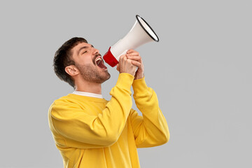 communication and people concept - young man in yellow sweatshirt shouting to megaphone over grey...
