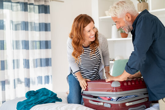 Happy mature couple closing suitcase